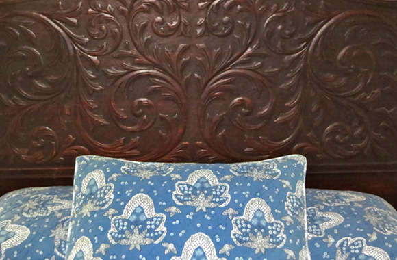Waipio Wayside, Plantation Room, decorative pillow in front of ornate headboard